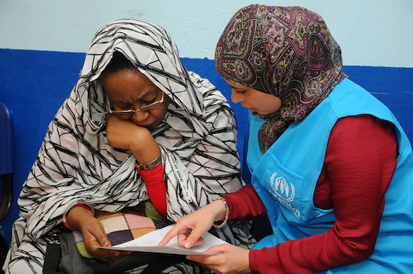 Nada rawash right, a unv reception coordinator with unhcr, is one of 40 egyptian national un volunteers. here, she is helping an asylum seeker fill out paperwork to become registered as a refugee with unhcr in egypt. g tech, 2014jpg